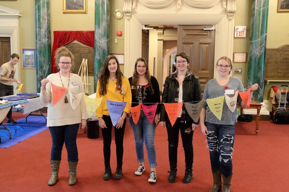 students holing flags that they created at the event