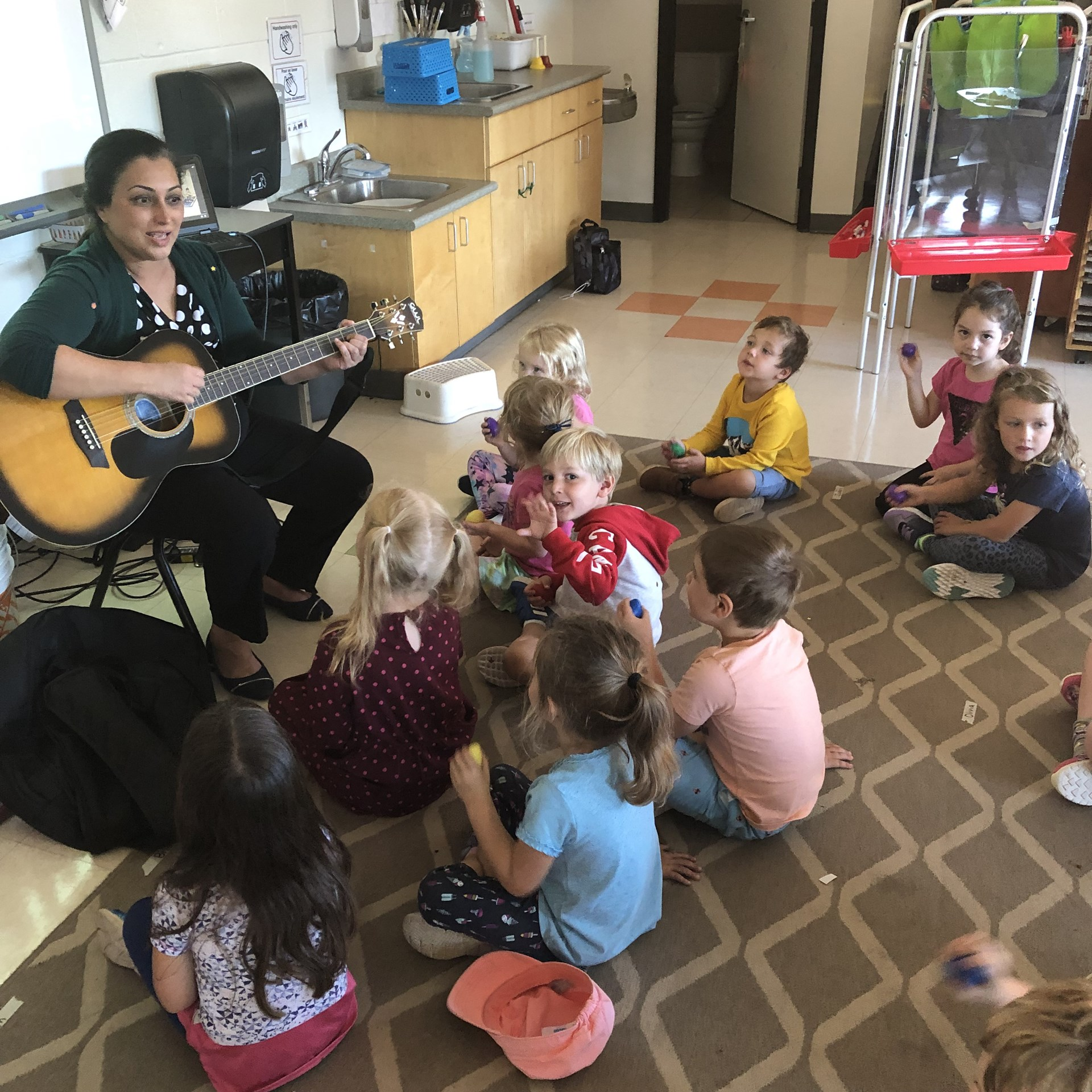 Children singing songs with teacher.