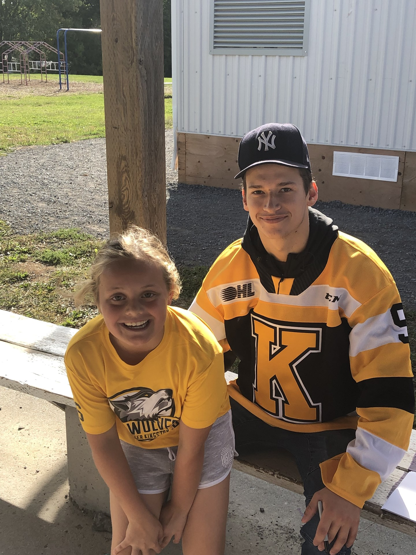 Kingston Frontenacs player sitting with student.