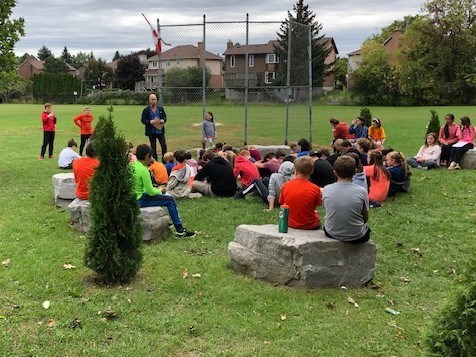 Students outside learning about the significance of Orange Shirt Day