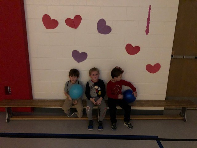 Boys sitting in front of Valentines Day poster.