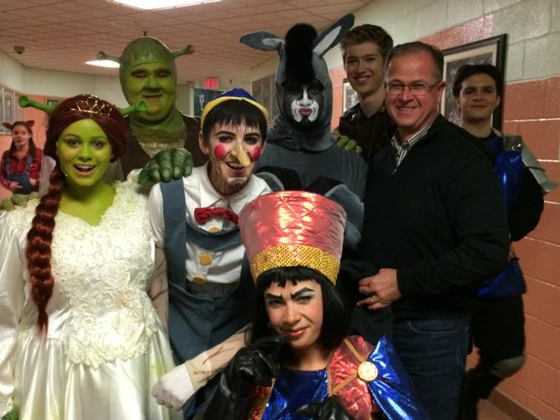The Director standing with characters for the play Shrek at Holy Cross.