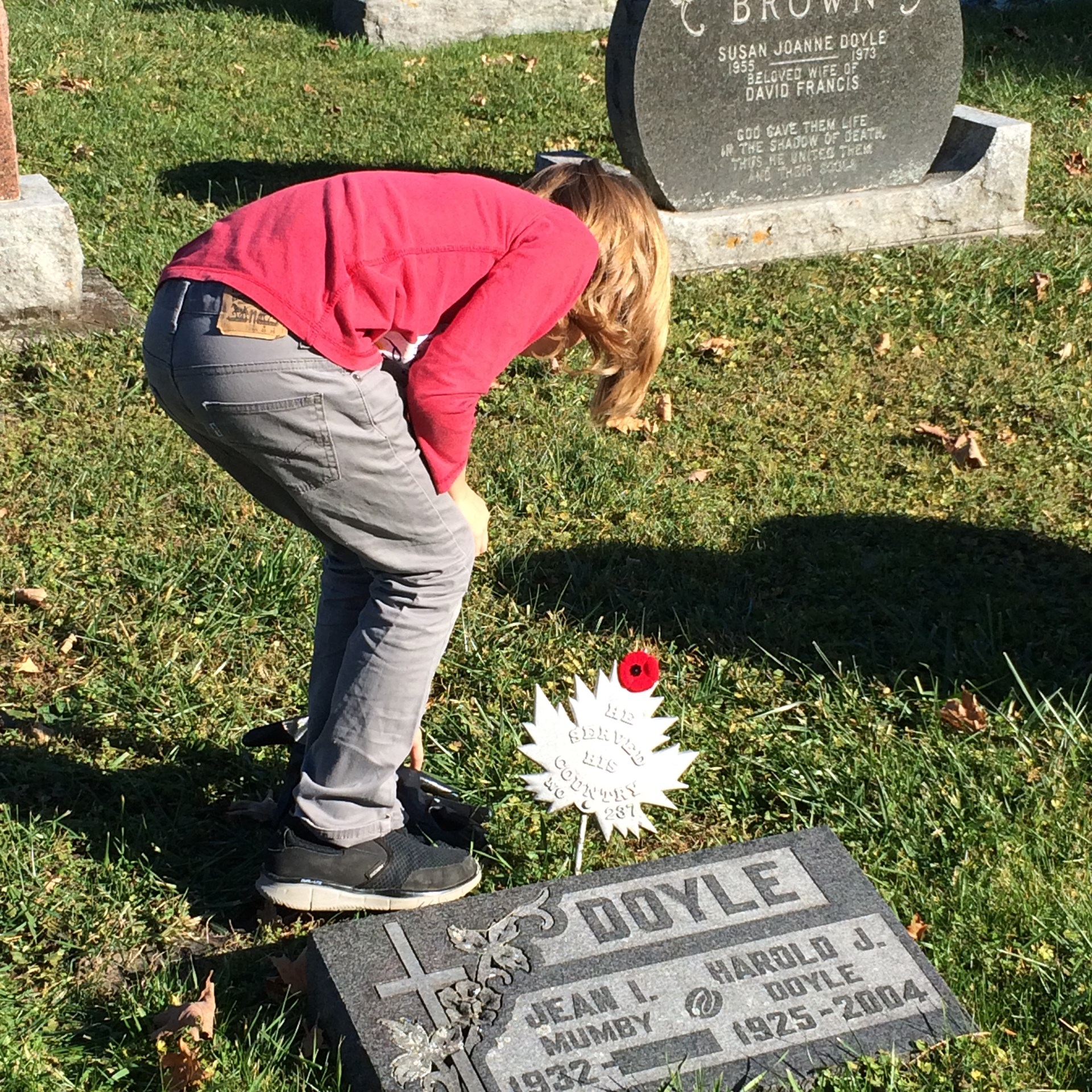 Student placing poppy on grave site.