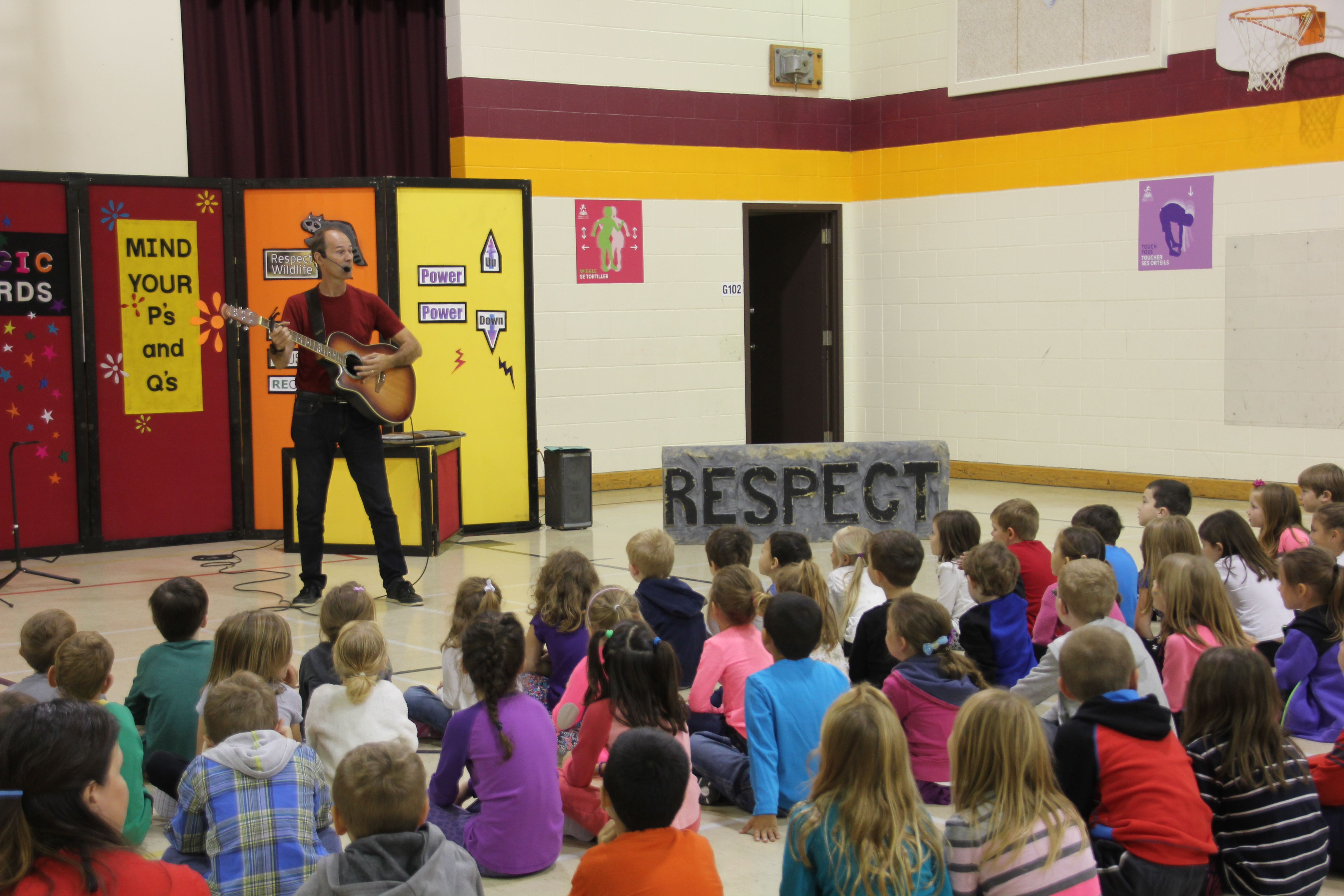Gerry Mitchell performing for a group of students.