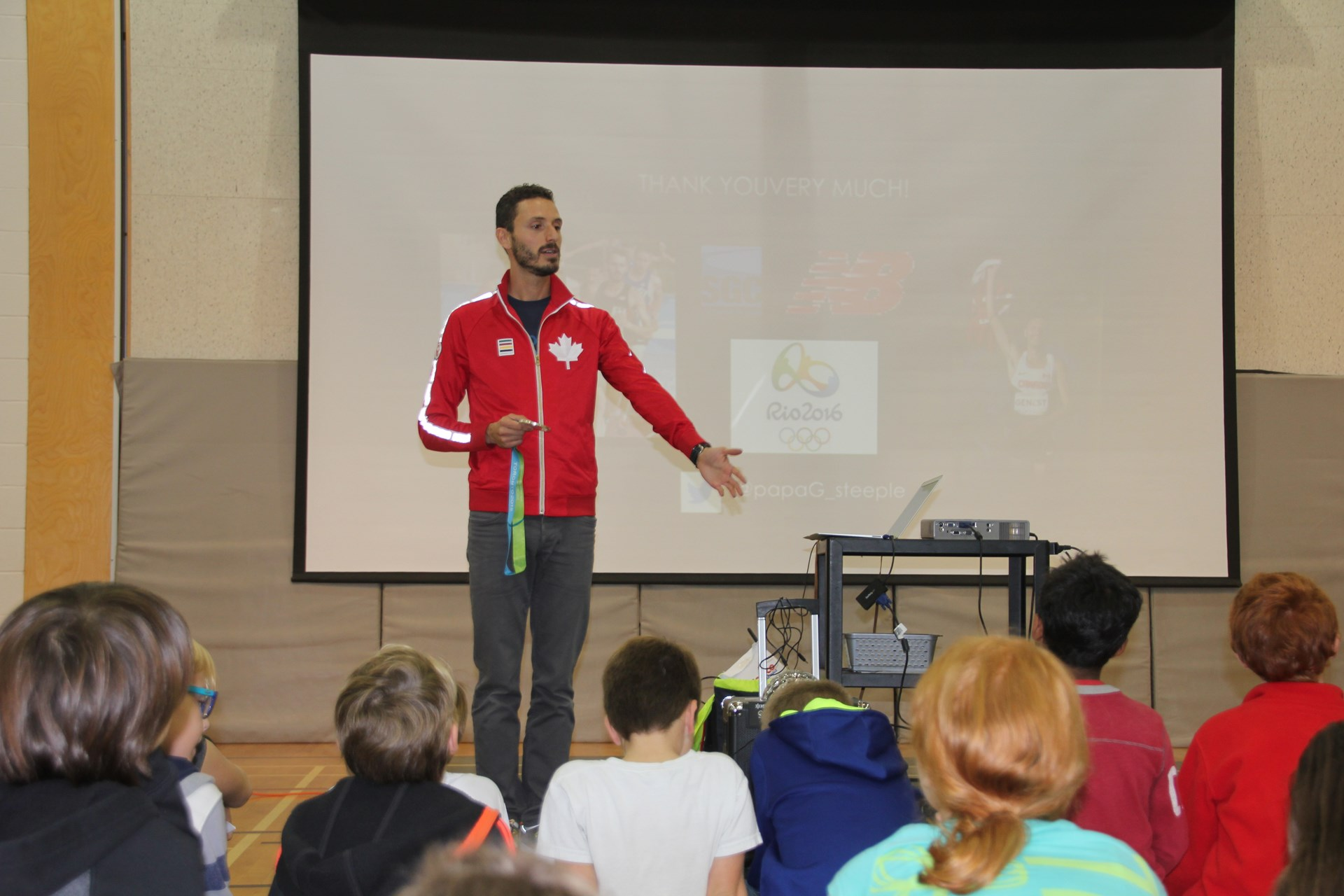 Olympian Alex Genest presenting to students.